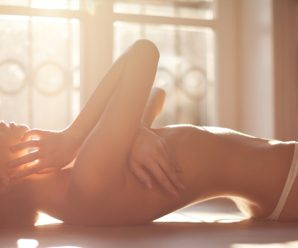 A beautiful young sensual woman lying on bed naked. Sunlight comes through the window and makes beautiful light withnice flare.